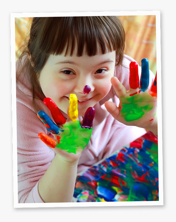 Photo of a smiling girl with paint on her hands